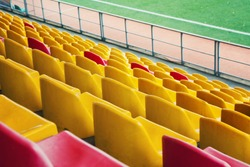 Empty stadium. Rows of yellow and red seats in stadium. Concept of empty stadium without spectators, quarantine time
