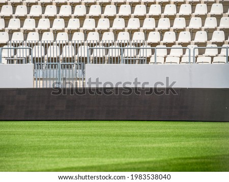 Empty stadium with white chairs in tribune and the green lawn grass Stock photo ©