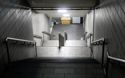 Empty stair looking down to dirty underground with trash spreading on the floor
