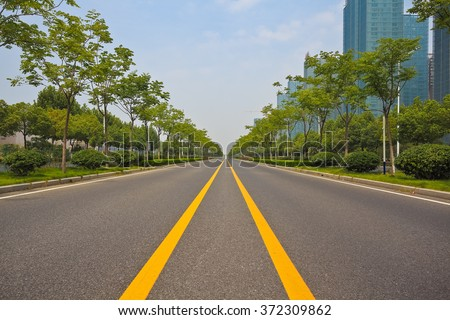 Empty straight line road surface with modern city buildings background