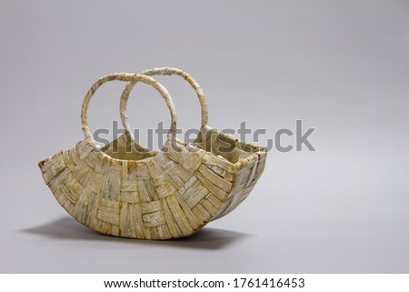 Empty straw wicker basket on a gray background. Fashionable bamboo basket, stylish interior item, eco design, handmade. Сток-фото ©