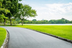 Empty street, green city park with blue sky. Pathway and beautiful trees track for running or walking and cycling relax in park on green grass field on the side. Sunlight and flare background concept