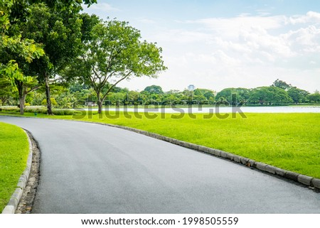 Empty street, green city park with blue sky. Pathway and beautiful trees track for running or walking and cycling relax in park on green grass field on the side. Sunlight and flare background concept Stock foto ©