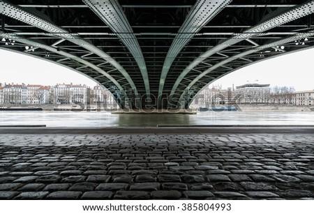 Empty street under a bridge in Lyon on a grey, winter day in February.