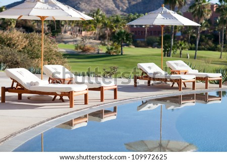 empty sunbeds by the beautiful resort pool