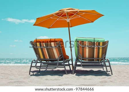Empty sunbeds with parasol in Miami Beach - stock photo