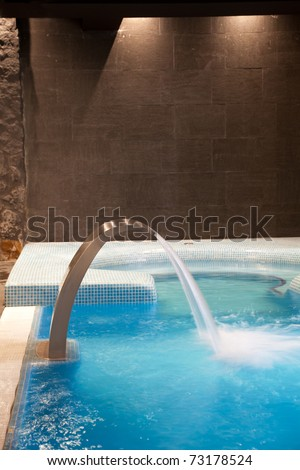 Empty Swimming pool with waterfall jet and jacuzzi in action