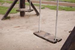 Empty swing on children playground,Children swing in the park,wooden swing,wooden swing on the lawn during