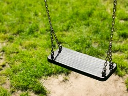 Empty swing on children playground. Green grass background. vacant chain swing for kids in a park. Corona virus causes empty playgrounds