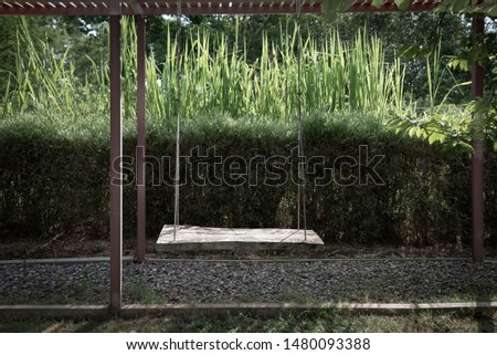 empty swing seat hanging in garden,means nobody own