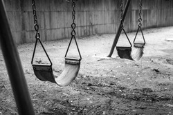 empty swings in black and white remind of childhood memories