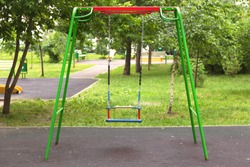Empty swings on the children's playground, the concept of