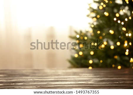 Empty table and blurred fir tree with yellow Christmas lights on background, bokeh effect. Space for design