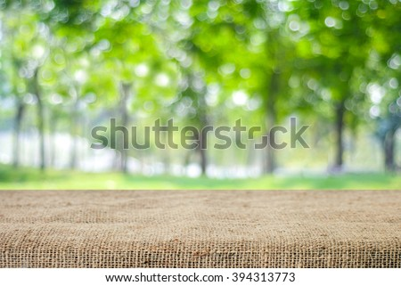 Empty table and sack tablecloth over blur tree with bokeh background, for product display montage