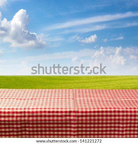 Empty table covered with checked tablecloth over green meadow and blue sky