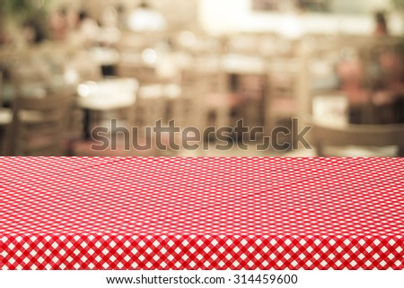 Empty table covered with red check tablecloth over blurred restaurant with bokeh light background, product, food display template