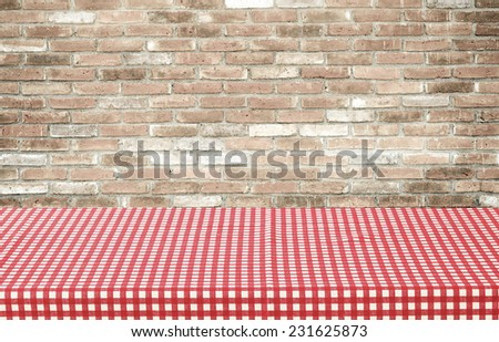 Empty table covered with red checked tablecloth over brick wall background, for product display montage