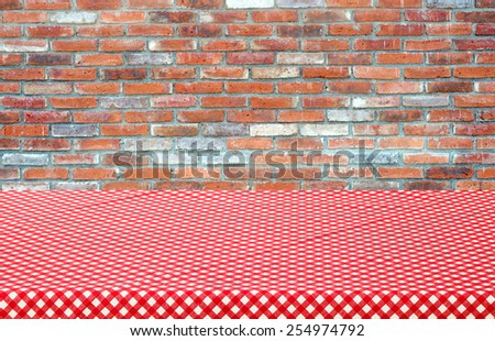 Empty table covered with red checked tablecloth over brick wall background, product display