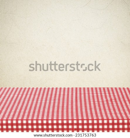 Empty table covered with red checked tablecloth over brown cement wall background, for product display montage