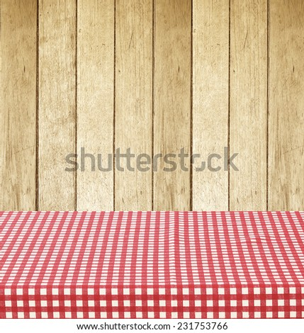Empty table covered with red checked tablecloth over vintage wooden wall background, for product display montage