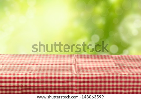 Empty table covered with tablecloth over bokeh garden background