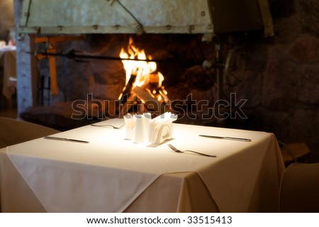 Empty table in a restaurant on the background of the fireplace with the fire.