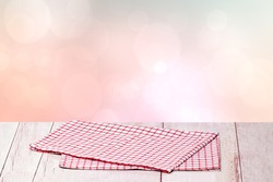 Empty table product. Closeup of a empty red checkered tablecloth or napkin on a rustic bright table over abstract pastel pink background. Template for your food and product display montage.