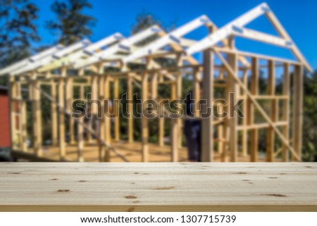 Empty table top for product display montage. House construction, framework blurred in the background.