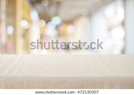 Empty table with linen tablecloth over blurred store with bokeh background, product display montage