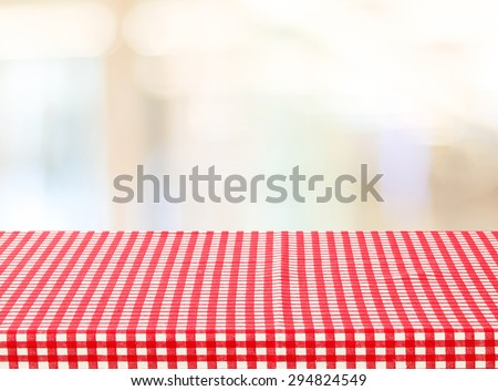 Empty table with red check tablecloth over blur festive bokeh background, product display