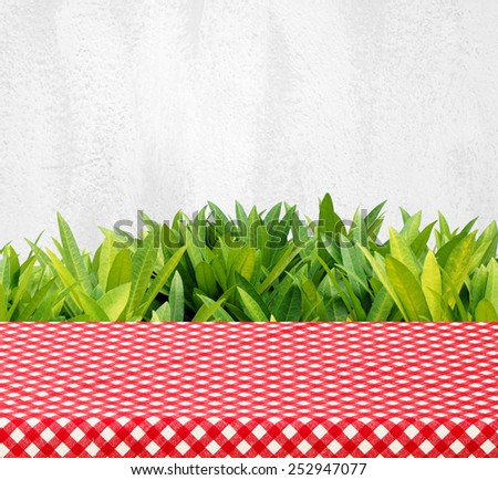 Empty table with red checked tablecloth over tree leaves and cement wall background, product display