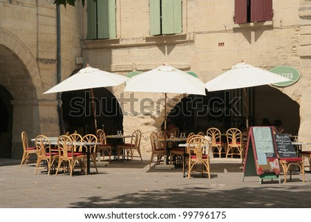 empty tables and chairs at sunny restaurant