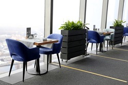 Empty tables in a restaurant with panoramic windows and view to the city. Security measures during the coronavirus pandemic