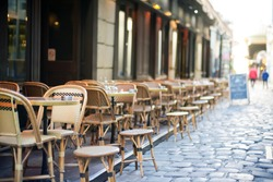 Empty tables in between dining hours along a Paris cobblestone alley