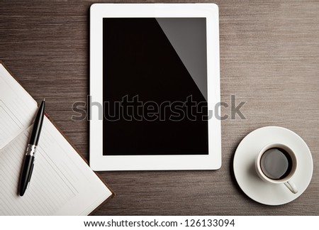 empty tablet and a cup of coffee on the desk