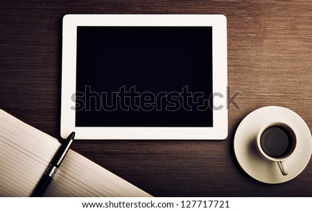 empty tablet pc and a coffee and notebook with pen on the office desk