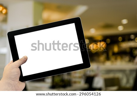 Empty tablet PC in hand in cafe bar interior with lamps