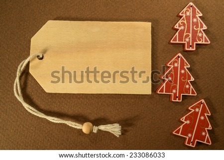 Empty tag with three Christmas decorations on brown background. Three Christmas decoration with price tag