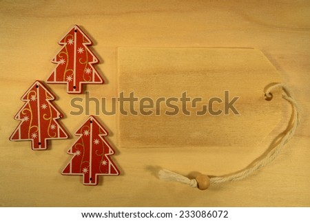Empty tag with three Christmas decorations on red background. Three Christmas decoration with wooden price tag