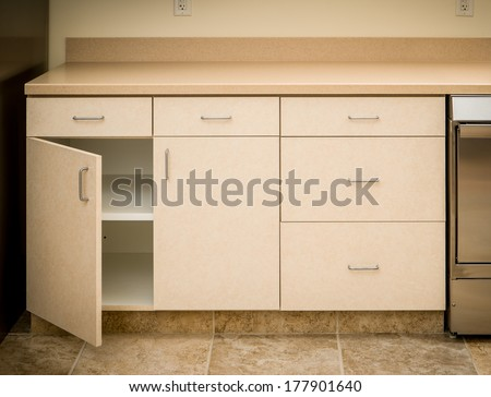 Empty tan kitchen counter and cabinet minimalist style with cabinet door open empty inside