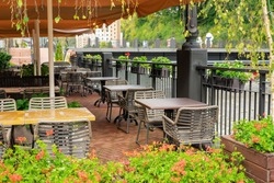 Empty terrace with tables and chairs in wood and metal at coffee and resteurant beside sidewalk in center city. Background business dramatic scene concept. Stay home concept