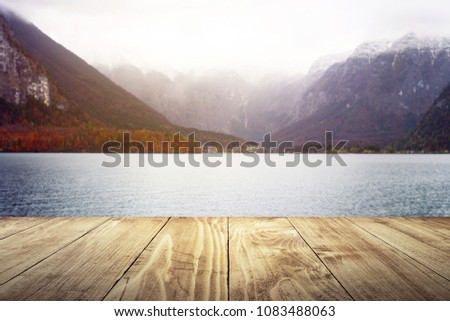 Empty texture wooden table with a lake background soft blurry, winter season, river front. Historic Village in Hallstatt with mountain, Austria. for your photomontage or product display.