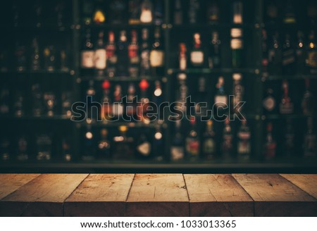Empty the top of wooden table with blurred counter bar and bottles Background /For montage product display or design key visual layout. #1033013365