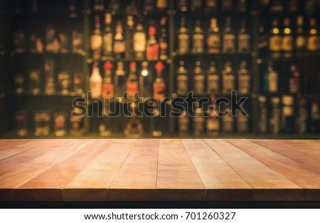Empty the top of wooden table with blurred counter bar and bottles Background /for your product display #701260327