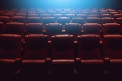 empty theater auditorium or movie cinema with red seats and blue light from behind