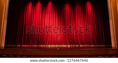 Empty theatre stage and red curtain or drapes background.Empty rows of red theater chairs.Seats in interior cinema for watching the show.Entertainment complex.