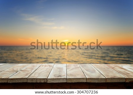 Empty top of wooden table or counter and view of tropical beach. For product display