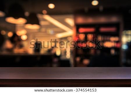 Empty top of wooden table or counter on cafeteria, bar, coffee shop background. For product display #374554153