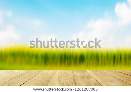 Empty top wooden table on yellow flowers field with colorful sky #1261209085