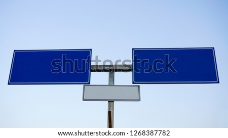 Empty traffic sign isolated on white background. Roadsign name arrow sign on blue sky. Large detailed roadside signage. Blanck copy space for text message. Clipping path. Directional road nameplate.